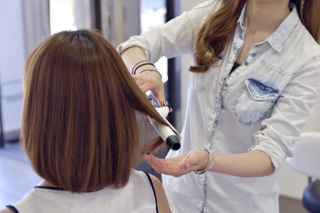 お客さんにヘアアイロンをする美容師